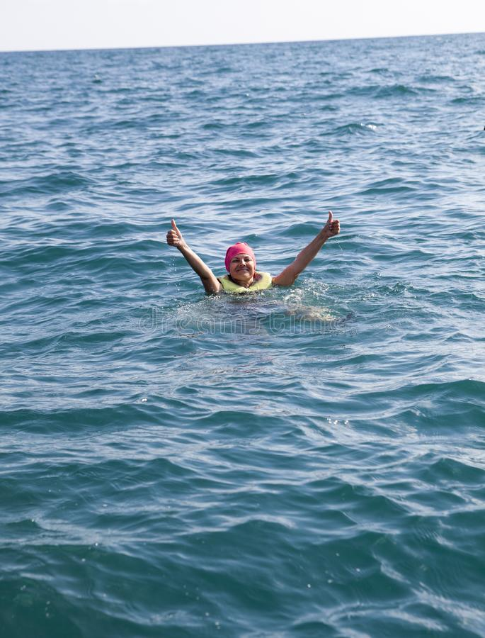 European woman staying afloat with cork lifesaving vest in open ocean and shows thumbs up. European woman staying afloat with cork lifesaving vest in open ocean stock images