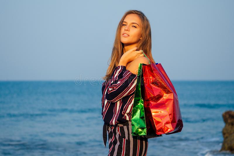 European woman in a stylish striped jumpsuit with shopping bags on the beach standing on a rock blue sea background with royalty free stock photos