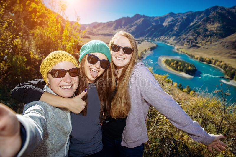 European women in sunglasses laugh doing selfie against mountain background. Young female hikers pose against amazing small island royalty free stock photography