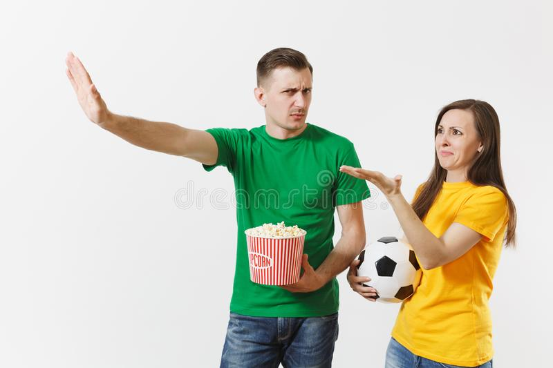 Dissatisfied couple, woman, man, football fans in yellow green t-shirt cheer up support team with soccer ball bucket of stock photos