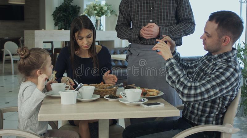 European young family having dinner at restaurant. Father shooting on his smartphone while waiter serving table. royalty free stock photos