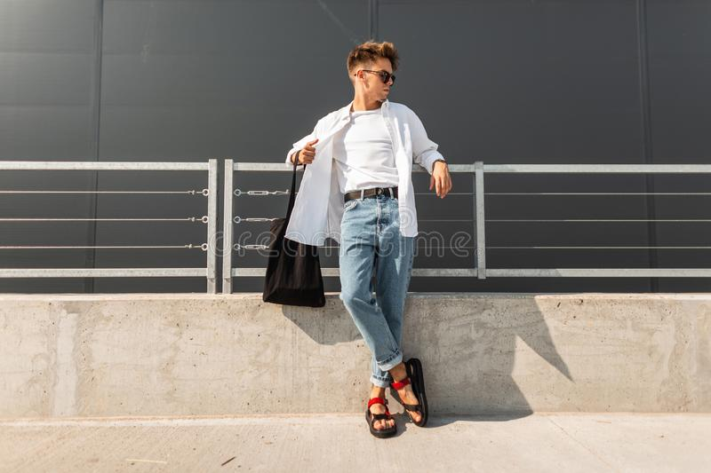 European young man model in stylish clothes in leather red sandals with a black bag in sunglasses is resting. Near the metal railing in the city. Handsome royalty free stock photos