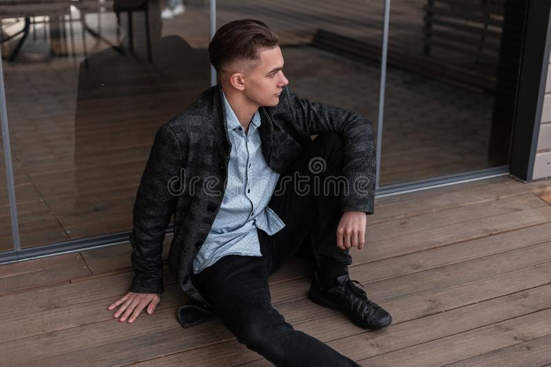 European young man with a stylish hairstyle in a trendy plaid jacket in a classic shirt in jeans in black shoes is resting. Sitting near the glass doors in a stock image