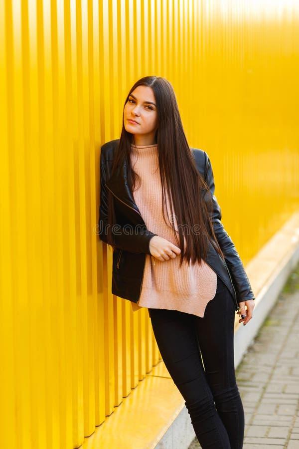 Europees meisje in een leerjasje, die zich dichtbij een muur bevinden royalty-vrije stock foto's