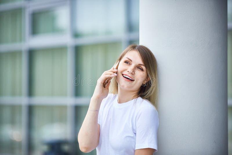 Europees meisje met recht haar die op de telefoon spreken stock afbeelding