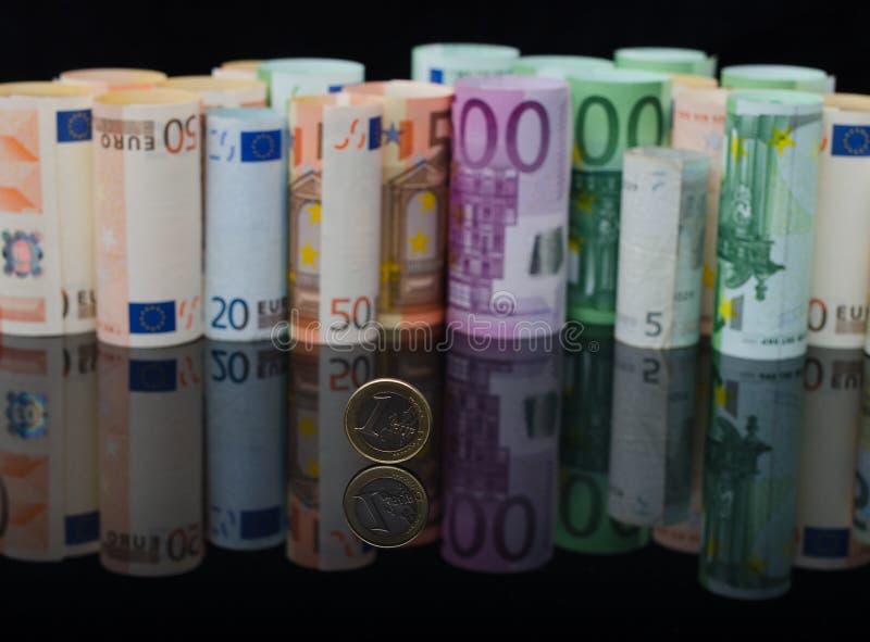 Europees papiergeld in broodjes en één euro muntstuk royalty-vrije stock afbeelding
