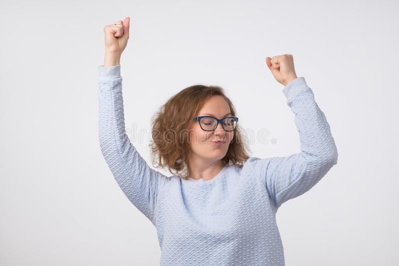 Europeisk flicka i blå skjorta som framme dansar av en grå vägg arkivfoton