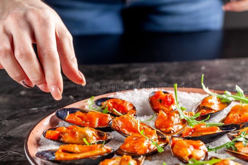 Europeisk kokkonst Pasta i kräm- sås med ädelost Marinerade musslor i tomatsås med rosmarin, vitlök, chili Portiondisk i restaura arkivfoton