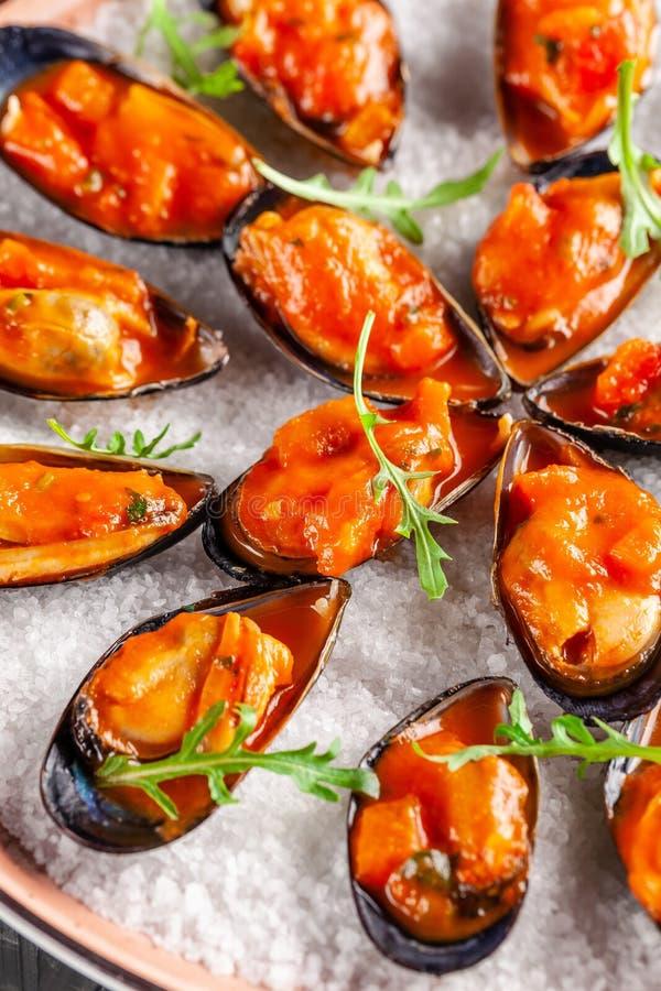 Europeisk kokkonst Pasta i kräm- sås med ädelost Marinerade musslor i tomatsås med rosmarin, vitlök, chili Portiondisk i restaura royaltyfri bild