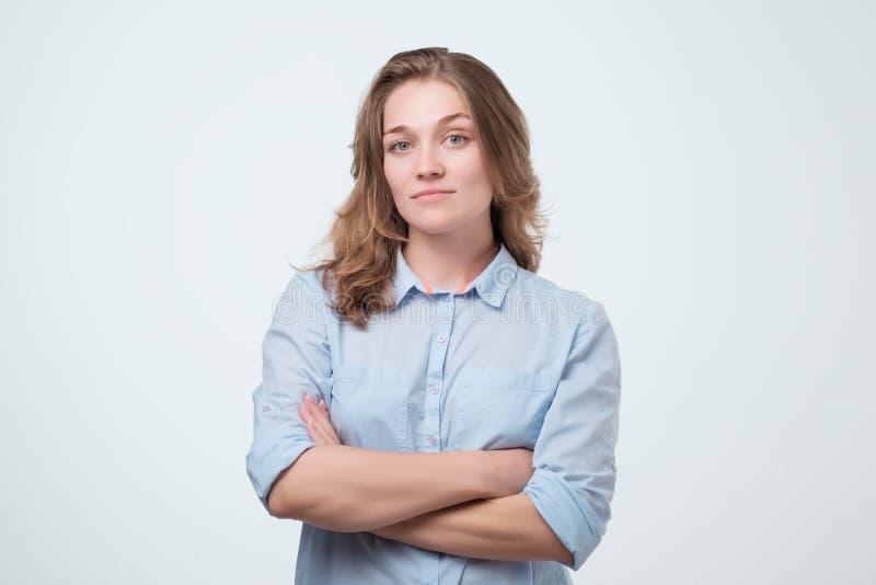 Europeisk kvinna i blå skjorta med allvarligt ansiktsuttryck royaltyfri bild