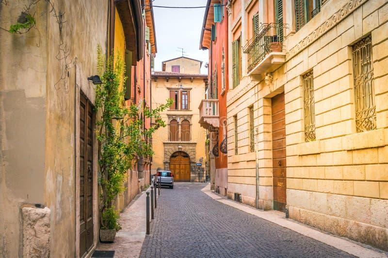 Europeisk liten smal kullerstengata med gamla ljusa hus, fönster med slutare i Verona, Italien royaltyfria bilder