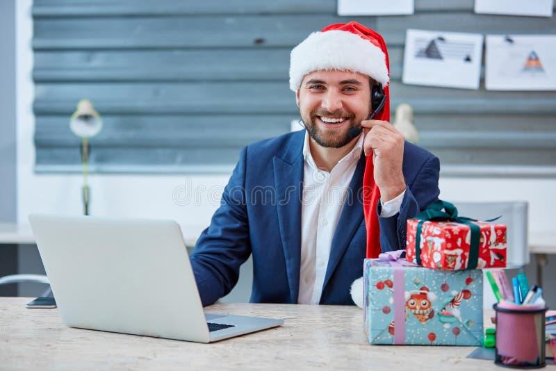 Europeisk manlig kontorsarbetare i en julhatt, dräkt och hörlurar på huvudet som sitter på skrivbordet med en bärbar dator och sk royaltyfri foto