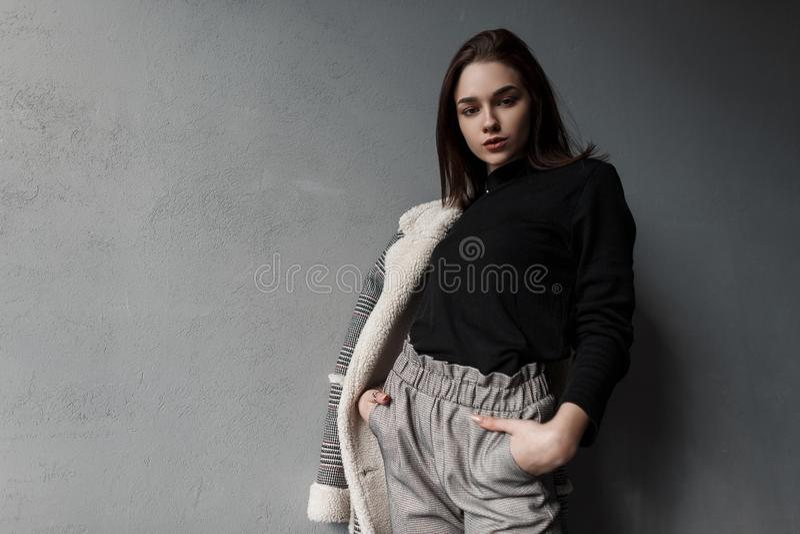 Europeisk modemodell av en ung kvinna i grå stilfull byxa i en svart skjorta i ett plädomslag som poserar anseende royaltyfri fotografi