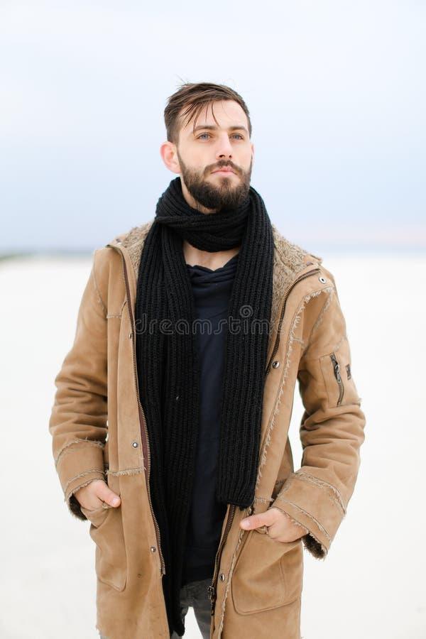Europeisk ung manlig person med bärande lag- och halsdukanseende för skägg i vit snöbakgrund royaltyfri bild