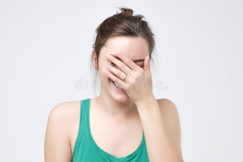 Europeiska kvinnliga fniss joyfully, täcker munnen, som försök stoppar att skratta arkivbilder