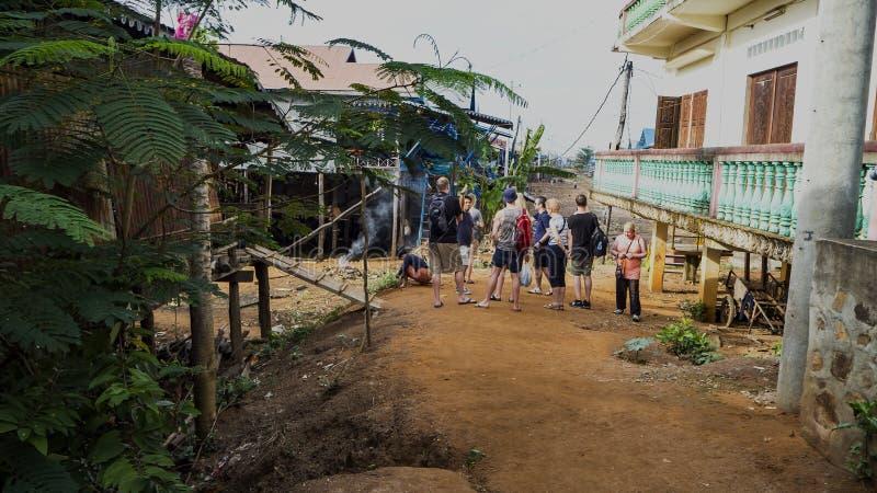 Europeiska turister, i att sväva byn Chong Knies i Cambodja, Tonle, underminerar den stora sjön hundar royaltyfria bilder