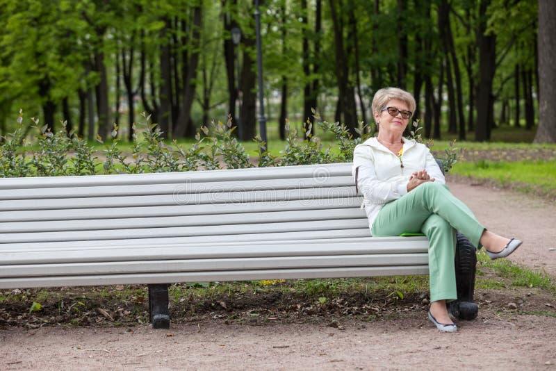 Europeiskt äldre kvinnasammanträde på kanten av bänken i sommaren parkerar, kopierar utrymme arkivfoto