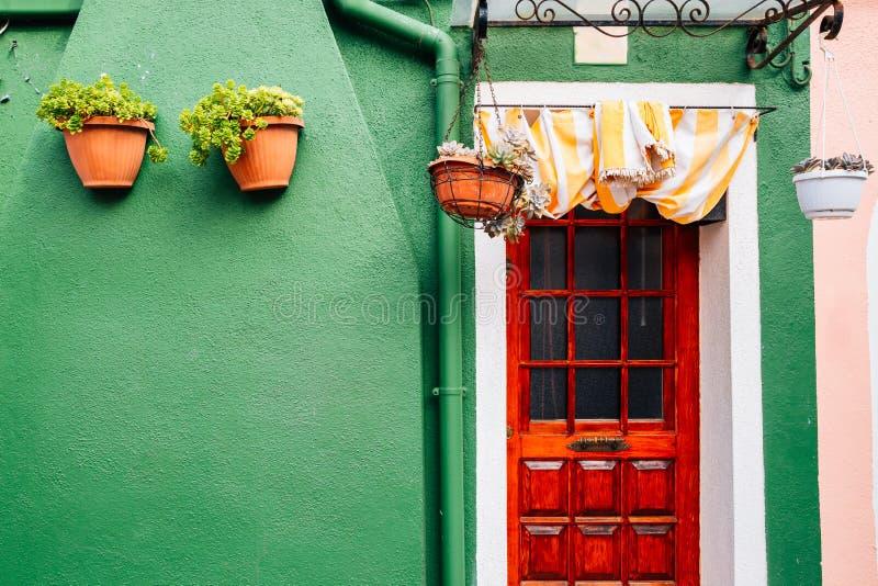 Europeiskt hus, grön vägg och trädörr i den Burano ön, Venedig, Italien royaltyfri fotografi