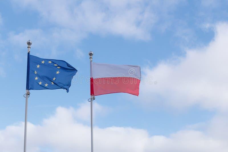 Europejczyk i Polska zaznaczamy obok siebie machać w wiatrze przeciw niebieskiemu niebu z chmurami obrazy stock