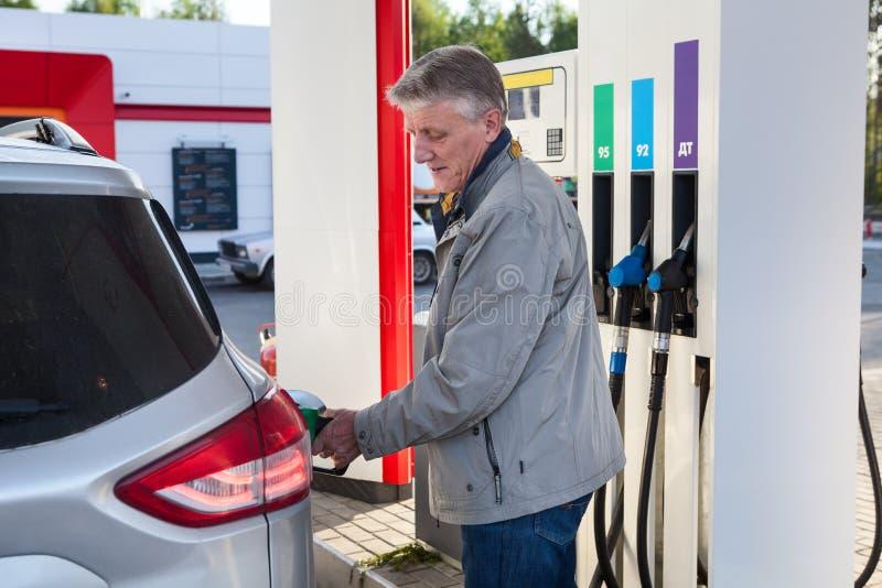 Europejczyka mężczyzna dojrzały refueling posiada pojazd na benzynowej staci przy lato sezonem zdjęcie royalty free