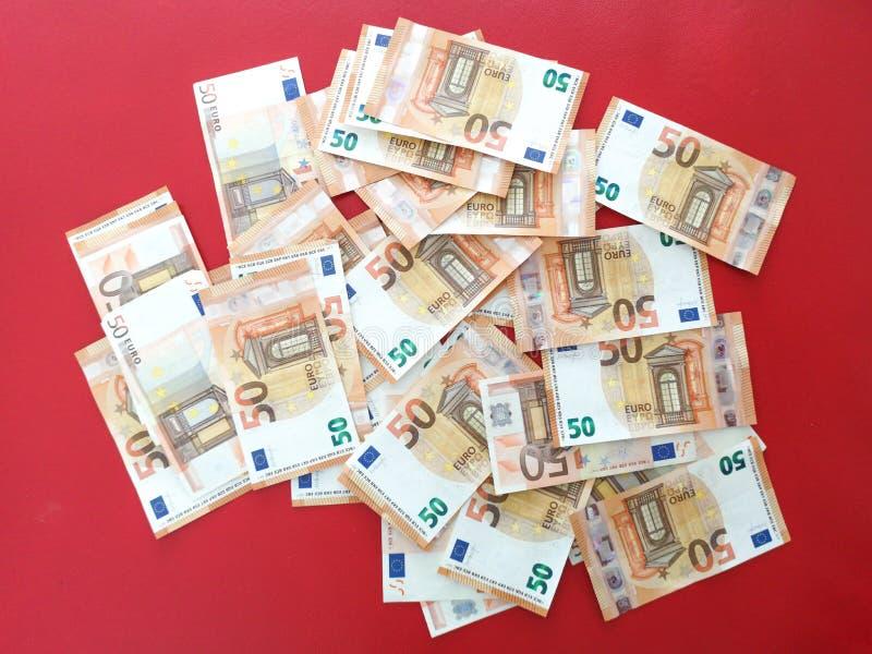 Europejscy pięćdziesiąt pieniądze euro rachunki na czerwonym chodniku, euro pieniądze przelewa się tło, euro banknoty zdjęcie royalty free