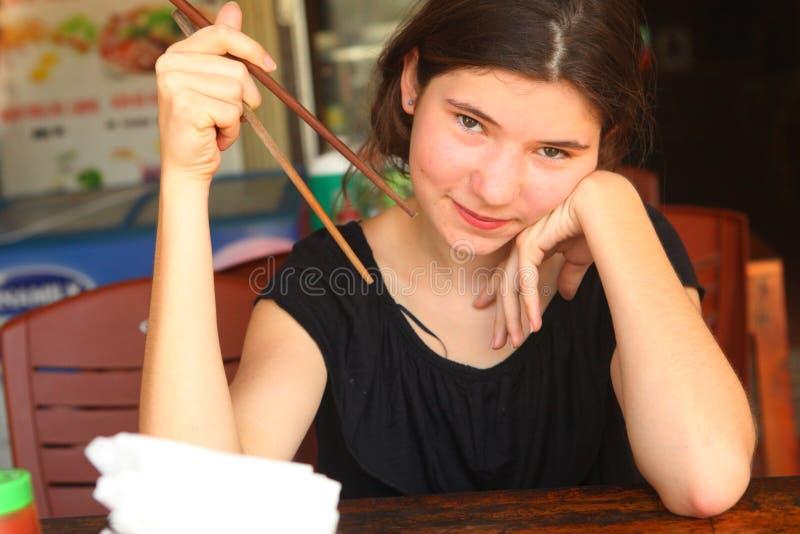 Europejska dziewczyna w azjatykci cukiernianym przygotowywającym próbować orientalną kuchnię obraz royalty free