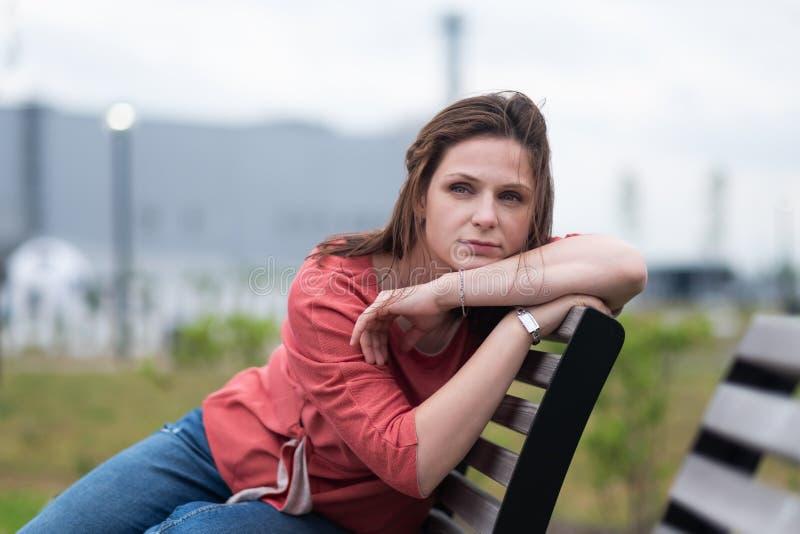 Europejska kobieta siedzi z przykrością w parkowym i patrzeje na boku obraz stock
