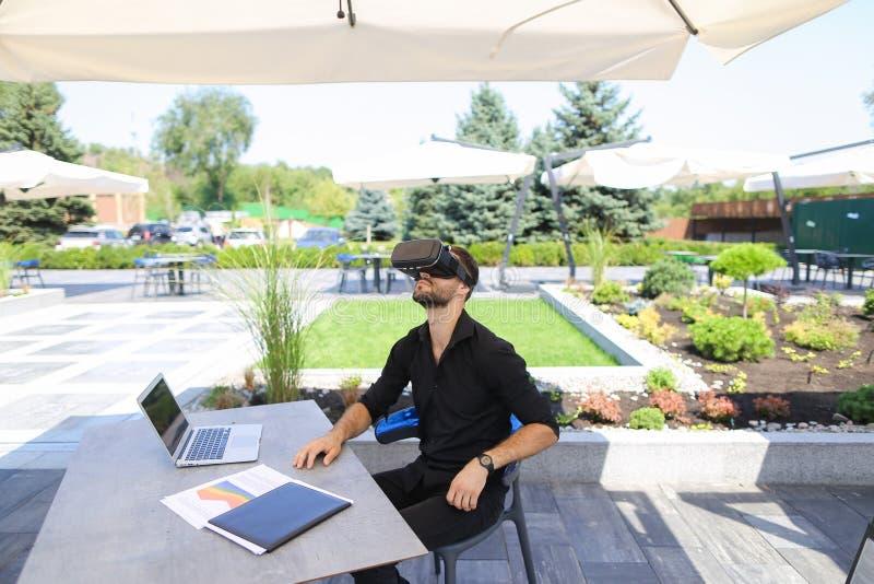 Europejski biznesmen cieszy się z rzeczywistość wirtualna szkłami, pracujący z laptopem outside i papierami zdjęcie stock
