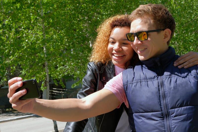 Europejski facet w okularach przeciwsłonecznych z ciemnoskórą piękną dziewczyną w kurtkach, robi selfie na tle zieleni drzewa obraz royalty free