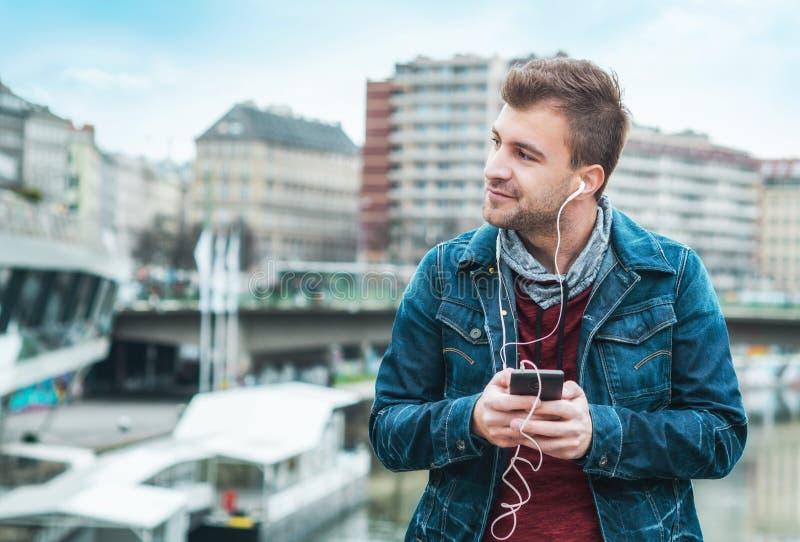 Europejski mężczyzna zabawa czas Muzykalny styl życia Rozochocony elegancki facet z smartphone słuchającą muzyką fotografia stock