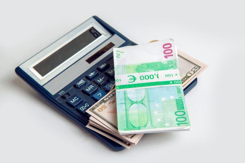 Europengar och dollar i packar ligger på räknemaskinen fotografering för bildbyråer