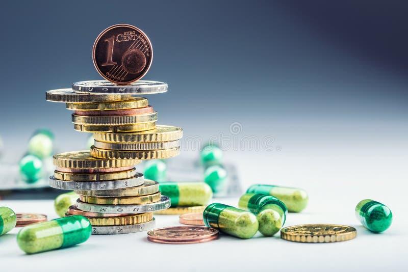 Europengar och medikament Euromynt och preventivpillerar Mynt som staplas på de i olika positioner och fritt preventivpillerar om royaltyfri bild