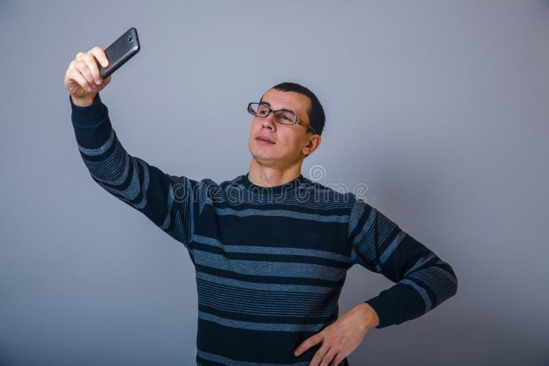 Europeo-mirada del hombre de 30 años que llevan a cabo una célula imagenes de archivo
