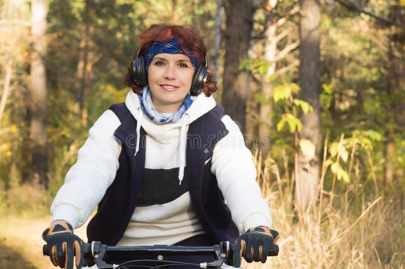 Europese aantrekkelijke vrouw in hoofdtelefoons in de herfstbos op royalty-vrije stock foto