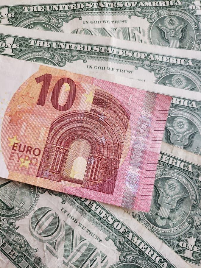 Europese biljetten van tien euro en Amerikaanse biljetten van één dollar stock fotografie