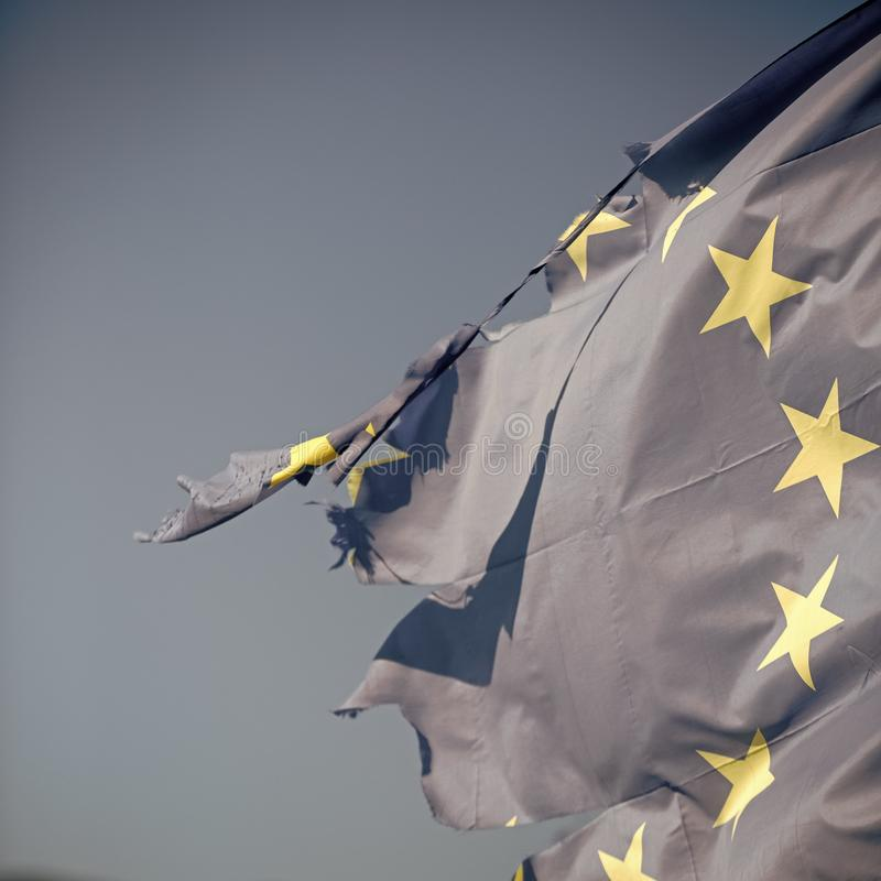 Europese die Unie twaalf stervlag en met knopen in wind op blauwe hemelachtergrond wordt gescheurd, sluit omhoog De vlag is weg g royalty-vrije stock afbeelding