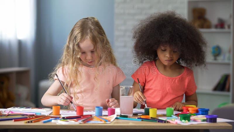 Europese en Afrikaanse vrienden bij het schilderen les in kinderenclub, creativiteit royalty-vrije stock afbeeldingen