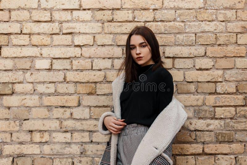 Europese jonge vrouw in een modieus geruit jasje met wit bont in retro stijl in uitstekende broek in T-shirt het stellen royalty-vrije stock foto's