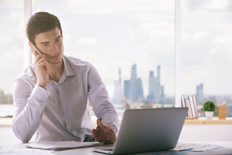 Europese mens op telefoon die laptop met behulp van stock afbeelding