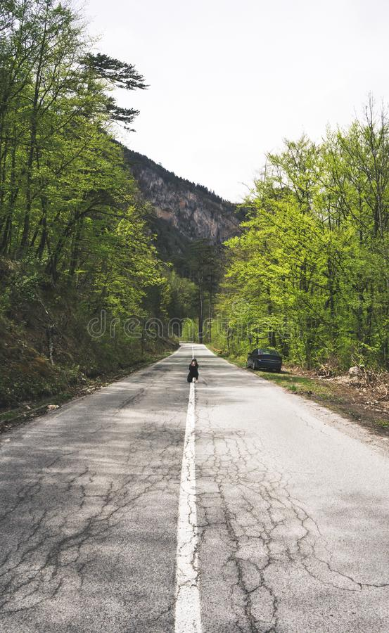 Europese reizigersvrouw die smartphone gebruiken die het platteland van de beeldenweg nemen en natuurlijk op de zomerdag Reiziger royalty-vrije stock foto