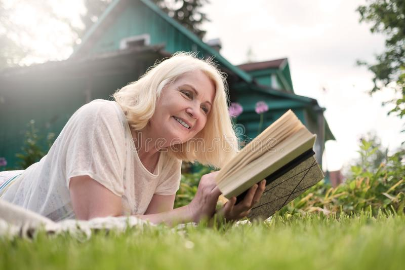 Europese rijpe blondevrouw die een boek in de tuin lezen stock foto's