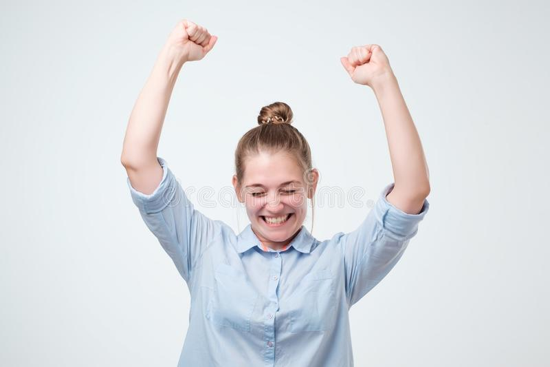 Europese sterke succesvolle jonge vrouwelijke winnaar die in blauw overhemd wapens opheffen die met vreugde en opwinding uitroepe royalty-vrije stock afbeelding
