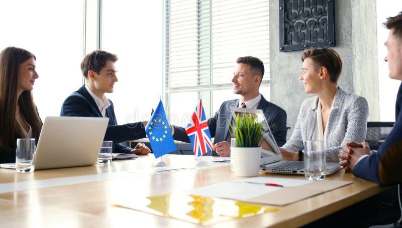 Europese Unie en van het Verenigd Koninkrijk leiders die handen op een overeenkomstenovereenkomst schudden stock afbeelding