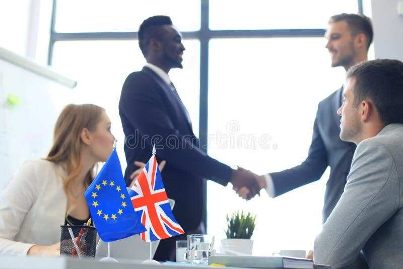 Europese Unie en van het Verenigd Koninkrijk leiders die handen op een overeenkomstenovereenkomst schudden Brexit stock afbeelding