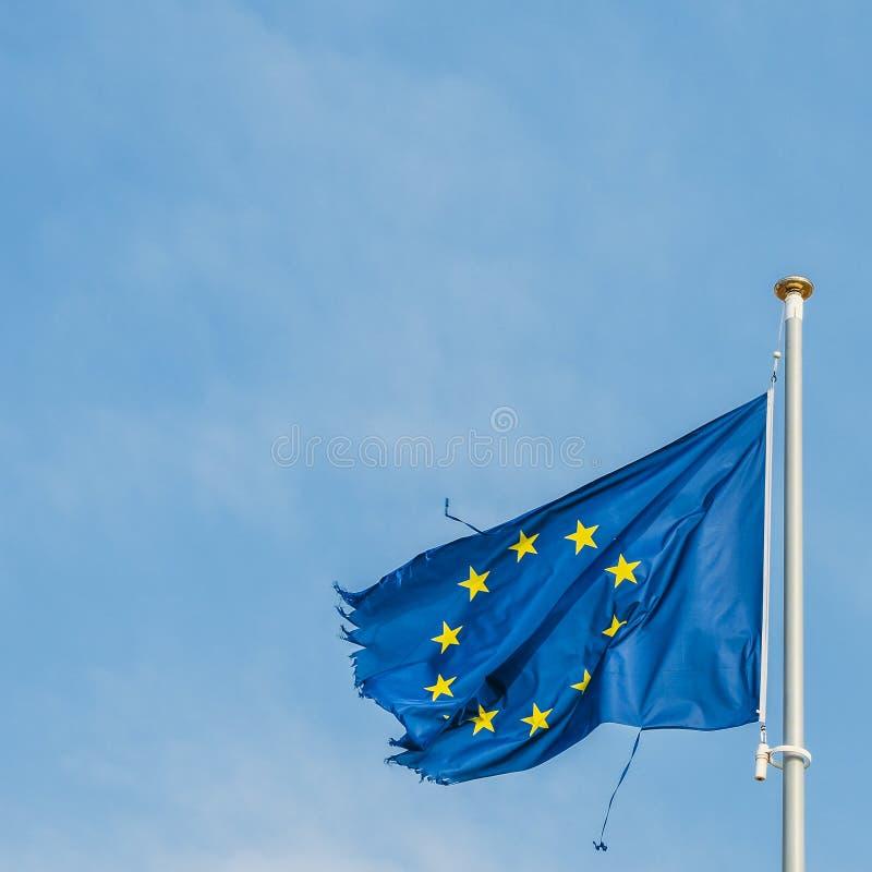 Europese Unie vlag op een mast die zich trots in de wind ondanks de gescheurde omhoog stukken van doek op de randen bewegen die i royalty-vrije stock foto's