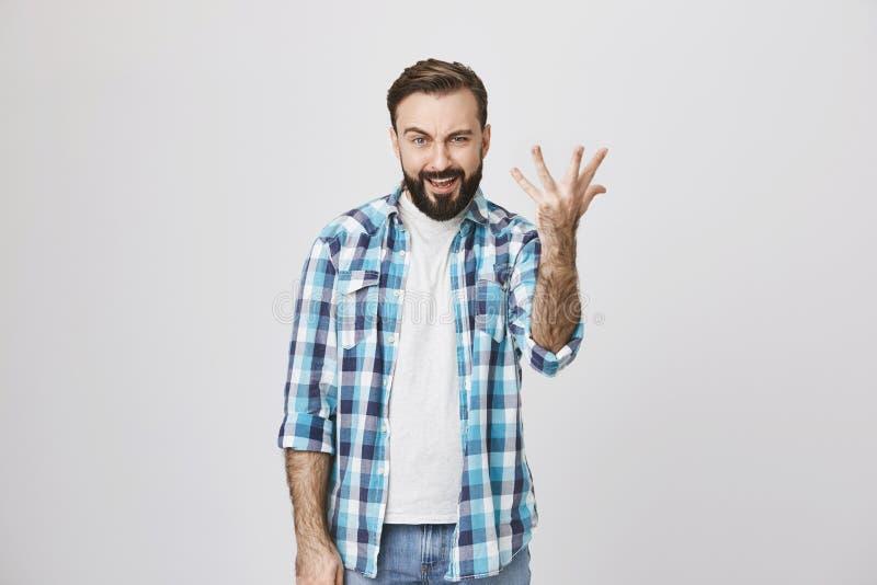 Europese volwassen mens die met baard hand met uitgespreide vingers opheffen die wat vragen, die plaid blauw overhemd dragen en stock foto
