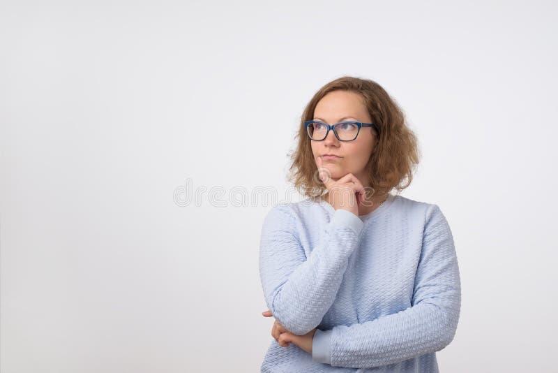Europese vrouw die in glazen omhoog bij het lege plaats en denken kijken Zij maakt plan voor dag stock foto's