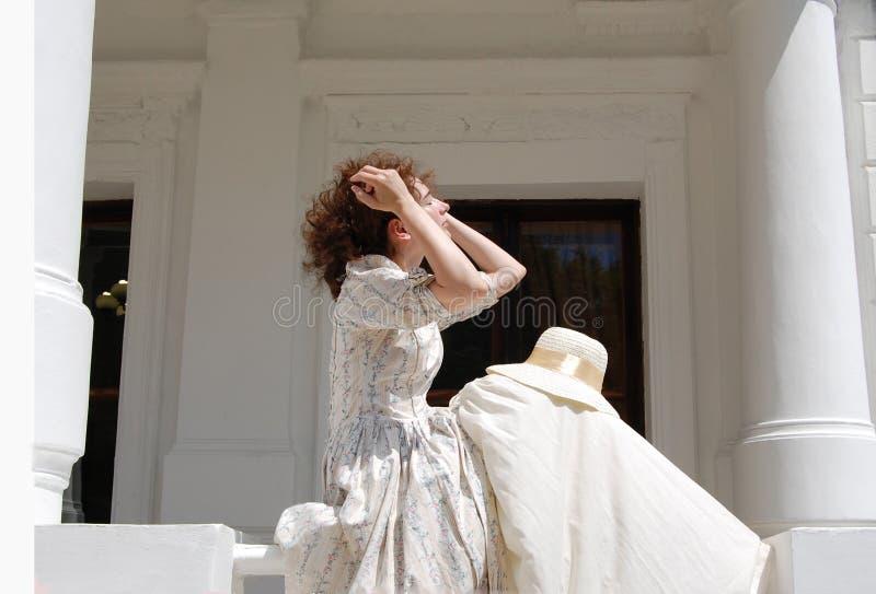 Europese vrouwenzitting in zonneschijn en wat betreft haar in uitstekende kleding dichtbij paleis stock foto