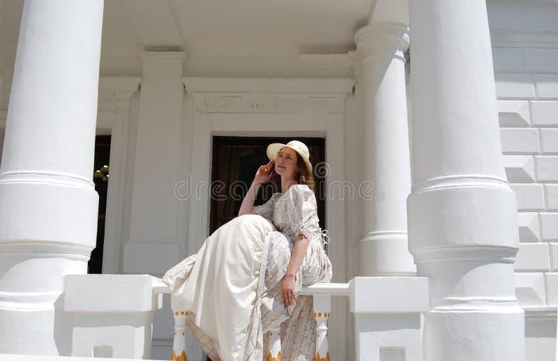 Europese vrouwenzitting in zonneschijn en wat betreft hoed in uitstekende kleding dichtbij paleis stock foto