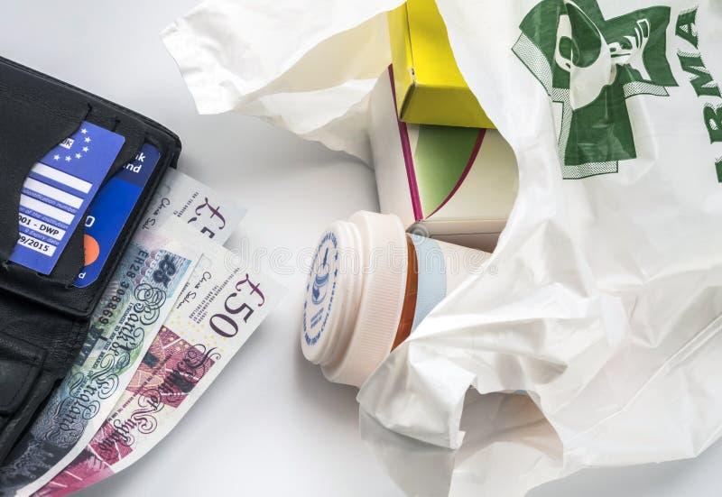 Europese ziekteverzekeringskaart in een portefeuille samen met verscheidene pond Sterling en geneesmiddelen in een zak, concept m royalty-vrije stock fotografie